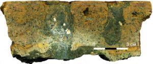 Рисунок 16. Слой глауконитового известняка толщи «дикарей» с ровной поверхностью «стекла» наверху, ржаво-желтой железистой пропиткой и крупными мешковидными норками, заполненными зеленым глауконитовым песчаником. Пришлифованный образец